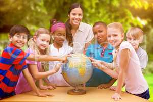 Composite image of cute pupils and teacher looking at globe in l