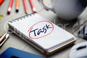 Task against notepad on desk