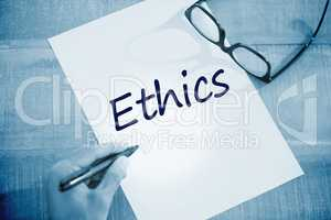 Ethics against left hand writing on white page on working desk