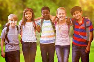 Composite image of smiling little school kids in school corridor