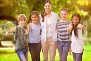 Composite image of cute pupils and teacher smiling at camera in