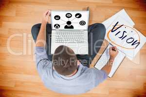 Vision against young creative businessman working on laptop