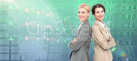 Composite image of serious businesswomen standing back on back
