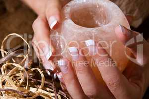 Woman?s hand with French manicure holding exotic salt-crystal candlestick