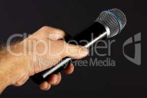 Classic microphone in performer hand isolated on black background