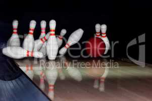 Bowling ball strike pins in front of dark background