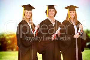 Composite image of three smiling students in graduate robe holdi