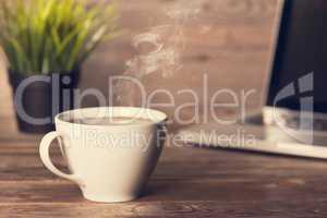 Hot coffee on wooden office desk