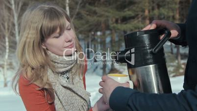 Young pair in wood. Man pours tea from a thermos.