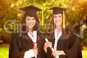 Composite image of two friends stand together after graduating