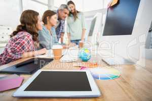 Tablet in the foreground with business people in the background