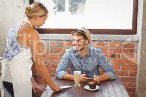 Handsome hipster smiling at blonde waitress