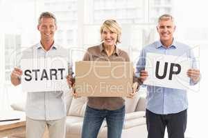 Smiling casual business people holding start up sign