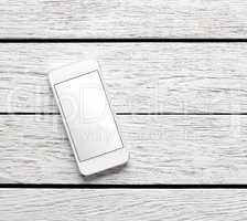 White smart phone on white wooden desk