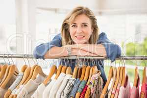 Smiling woman leaning on clothes rail