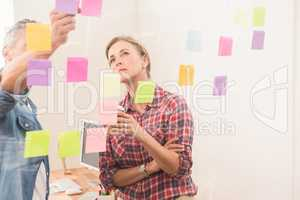 Casual business colleagues working with sticky notes