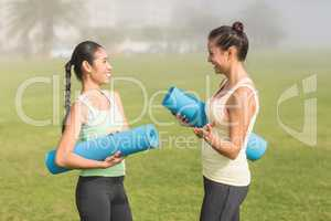 Sporty women with exercise mats chatting