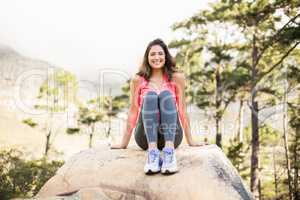 Young happy jogger sitting on rock