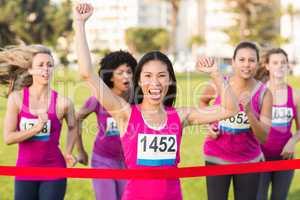 Cheering woman winning breast cancer marathon
