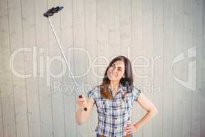 Pretty hipster taking a selfie with stick