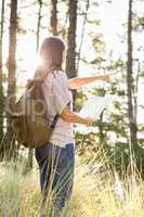 Brunette hiker with map pointing far away