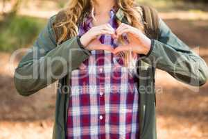 Blonde hiker framing heart with hands