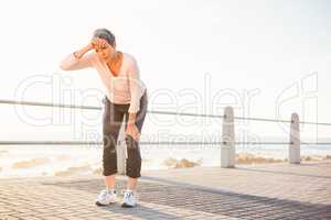 Sweating sporty woman resting at promenade