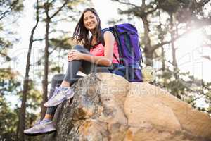 Young happy jogger sitting on rock and looking at camera