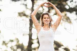 Pretty young jogger shaping heart with hands