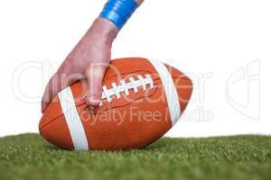 American football player placing the ball