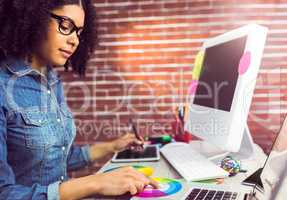 Casual female designer working with digitizer and colour chart