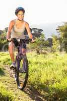 Smiling athletic brunette mountain biking