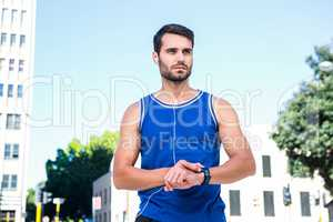 Handsome athlete setting heart rate watch