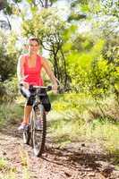 Smiling blonde athlete mountain biking