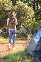 Brunette camper walking away from tent