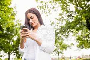 Beautiful brunette sending a text message