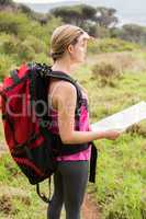 Blonde hiker with map searching for path