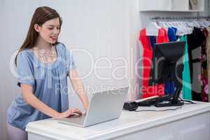Shop worker using laptop by the till