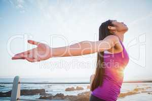 Carefree fit woman with arms outstretched at promenade