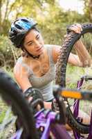 Athletic brunette checking her mountain bike