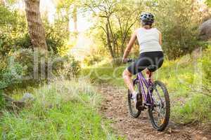 Athletic brunette mountain biking on path