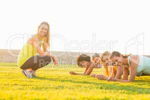 Smiling sporty women planking during fitness class