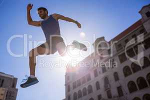 Handsome athlete leaping in front of building