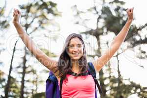 Young happy jogger sitting on rock and cheering