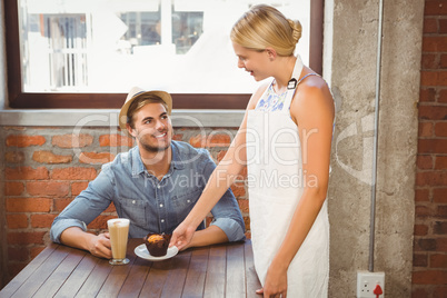 Smiling blonde waitress serving muffin to handsome hipster