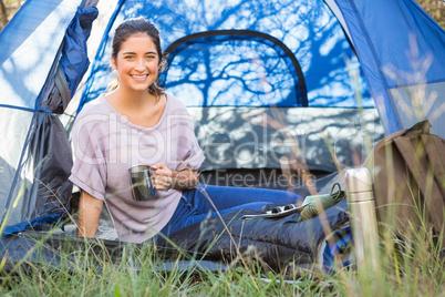 Smiling brunette camper sitting in tent