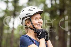 Young pretty happy biker taking off helmet