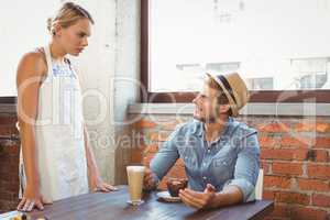 Handsome hipster talking to blonde waitress