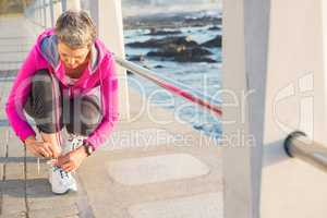 Sporty woman tying her shoelace at promenade