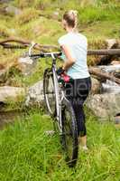 Rear view of a fit woman rolling her bike